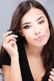 Pretty woman applying mascara on her lashes — Stock Photo