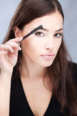 Pretty woman combing her eyebrow — Stock Photo