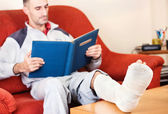 Man with a broken leg on a sofa at home reading book — Stock Photo