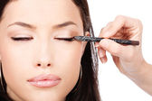 Applying cosmetic pencil on closed eye — Stock Photo