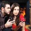 Romantic couple near fireplace drinking red wine — Stock Photo
