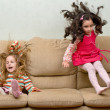 Two little girls jumping on sofa — Stock Photo