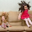 Stock Photo: Two little girls jumping on sofa