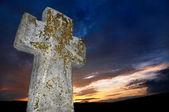 Brightly lit stone cross — Stockfoto