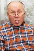 彼の舌を示すシニア男性. — ストック写真