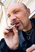 Typical criminal with cigarette — Stock Photo