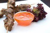 Kebabs on sticks with hot sauce — Stock Photo