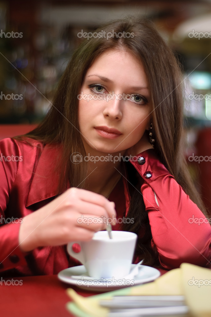 Brunette girl drinks tea or coffe in cafe — Stock Photo #7796628