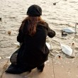 Lonely girl with swans - Stock Photo