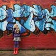 Little girl in front of a brick wall with graffiti — Stock Photo
