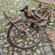 Very rusty bicycle lying on cobble-stones — Stock Photo