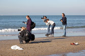 Five photographers on a beach — Stock Photo