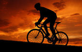 Cyclist riding a road bike at sunset — Stock Photo