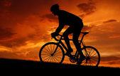 Велосипедист, езда на велосипеде по дороге на закате — Стоковое фото