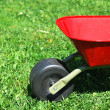 Foto Stock: Red handbarrow in garden.
