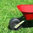 Foto de Stock  : Red handbarrow in garden.