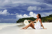 Attracrive girl sitting on the sand of a tropical beach — Stock Photo