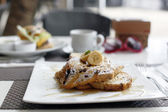 Cinnamon raisin french toast with maple syrup and fresh bananas — Stock Photo