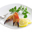 Crab claws, lemon wedges and a sprig of parsley on a platter. — Stock Photo
