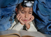 Boy reading a book under the covers with a flashlight — Foto Stock
