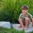 Portrait of a young boy, sitting on a rock. - Stock Photo