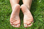 Women's feet in the grass. — Stock Photo