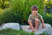 Portrait of a young boy, sitting on a rock. — Stock Photo