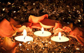 Lighted candles on a golden background with rose petals. — Photo