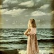 Little girl on the beach. stylized old photo — Stock Photo