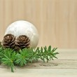 Pine branch with pine cones and Christmas decorations on a board background — Stock Photo
