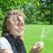 Stock Photo: A young girl blow bubbles.