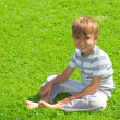 Royalty-Free Stock Photo: Portrait of a young boy sitting in the grass