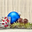 Photo: Pine branch with pine cones and Christmas decorations on a board background