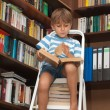 Boy in library reading book — Stock Photo