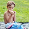 Boy eating a sandwich at a picnic. — Stock Photo