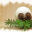 Pine branch with pine cones and Christmas decorations on a board background — Stock Photo #7959310