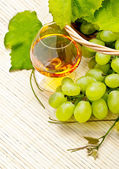 Bunch of white grapes in a basket and a glass of wine — Stock Photo
