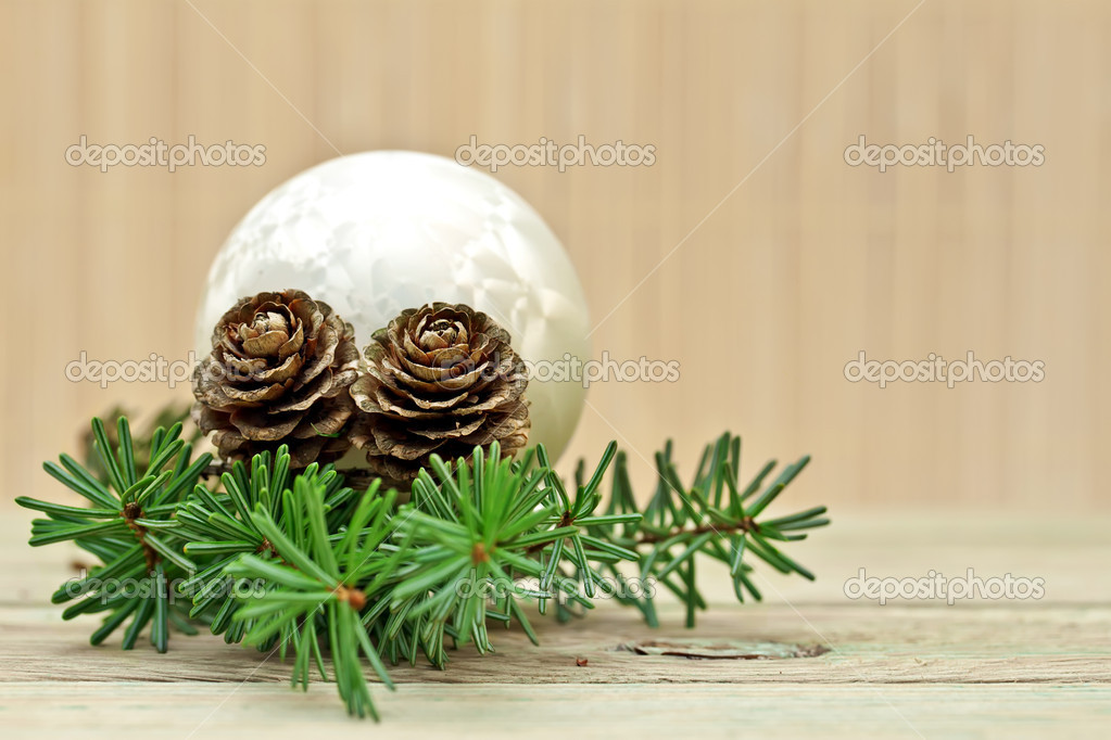 Pine branch with pine cones and Christmas decorations on a board background.  Stock Photo #7959257