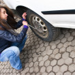 Young woman during the wheel changing — Stock Photo #7919397