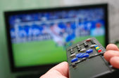 Football match and remote control — Stock Photo