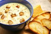 Cheese soup with toasts in blue pottery — Stock Photo