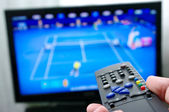 Remote control and tennis match — Stock Photo