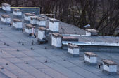 Flat roof with many chimneys — Stock Photo