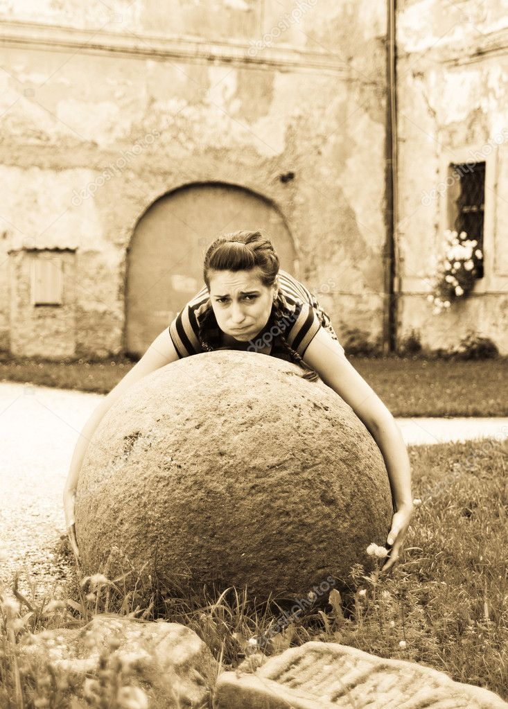 Young woman try to raise big stone ball — Stock Photo #7916205