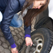 Young woman during the wheel changing - Stock Photo