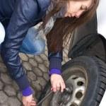 mujer joven durante el cambio de rueda — Foto de Stock
