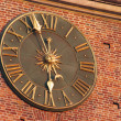 Golden clock in red wall of city hall tower in Krakow, Poland — Stock Photo #7930512