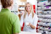 Gyógyszerész ad gyógyszert, vevő