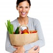 thumbnail of Pretty woman holding a grocery bag and smiling on white