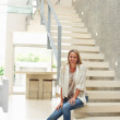 thumbnail of Happy mature woman sitting on modern stairs in a spacious ho